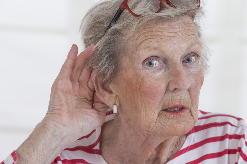 older woman holding ear to hear