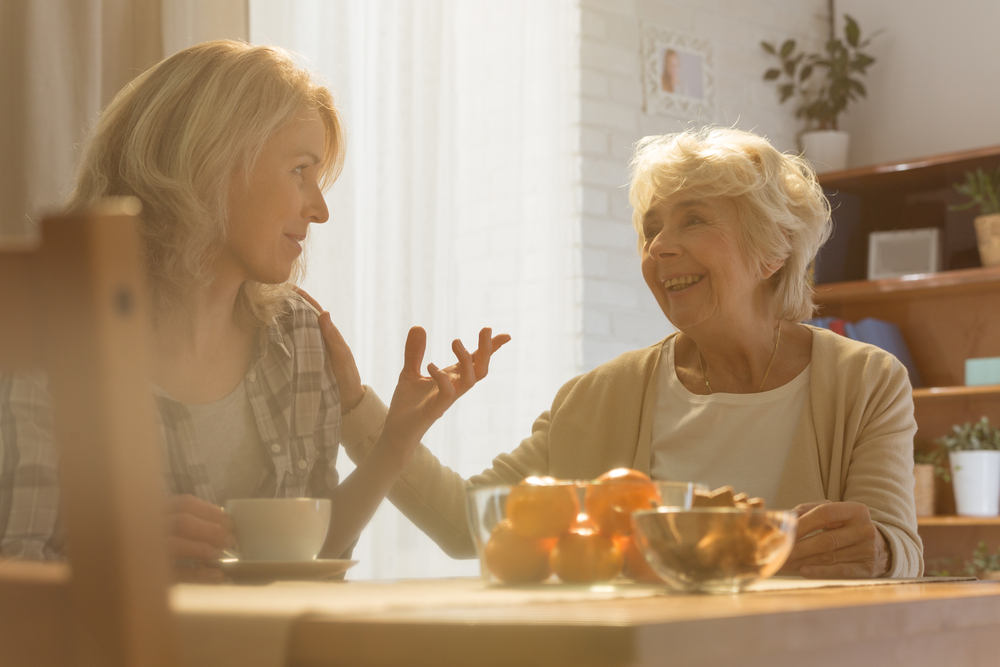 adult daughter chatting with elderly mother